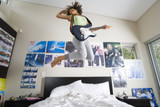 Teenage girl (16-18) playing electric guitar, jumping in air above bed, low angle view