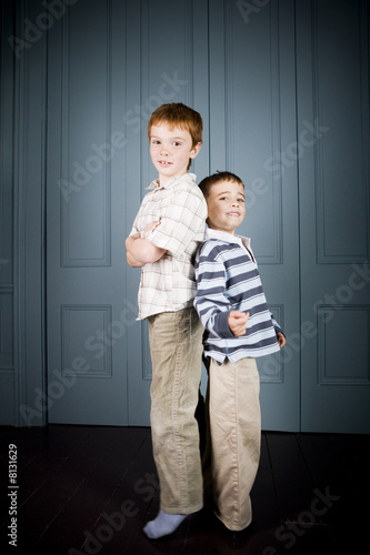 Older and younger boy standing back to back
