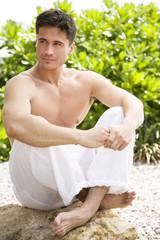 Topless man sitting cross-legged on a rock in the sun