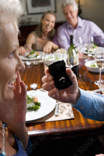 Two mature couples having lunch at table, man holding engagement ring by woman in foreground