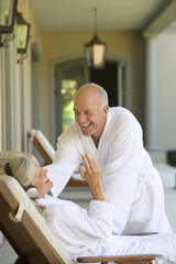 Mature couple wearing white bath robes, man smiling at woman wearing headphones lying in deck chair