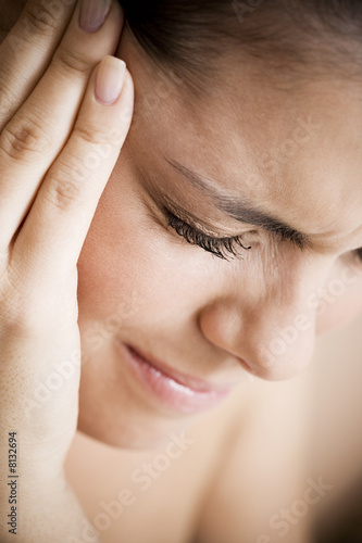 Woman with toothache or headache, holding her hand to her temple