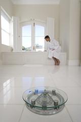 Young woman wearing bath robe, sitting by bath