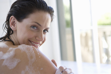 Young woman in bubble bath, smiling, portrait