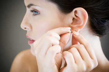 Woman putting in earrings