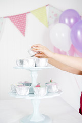 girl's hand taking cake from cake stand at birthday party