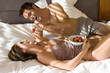 Young man holding strawberry above woman's mouth in bedroom