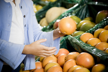 Cropped image of a girl selecting grapefruits in a supermarket.
