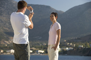 A man taking a photo of his partner on holiday