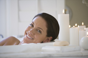 Young woman in bubble bath by candles, smiling, portrait
