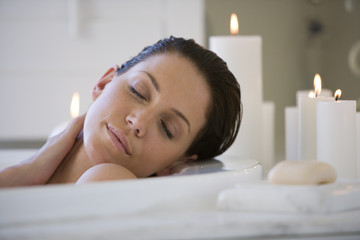 Young woman in bubble bath by candles, eyes closed, close-up