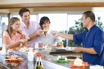 Three friends eating in sushi bar, smiling at chef