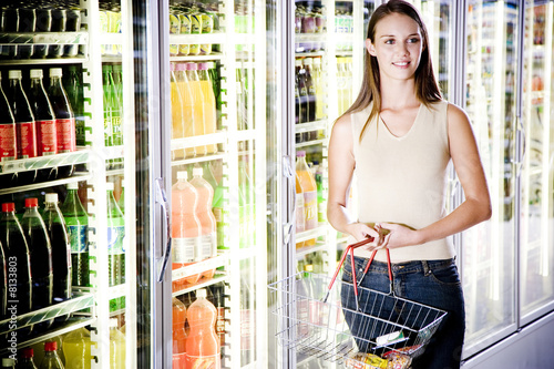 Woman stood next to a refrigerator door in a supermarket