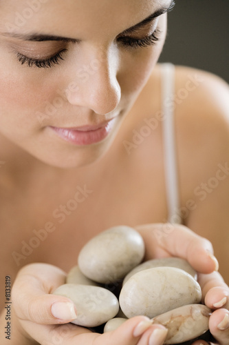Woman holding stones for hot stone therapy