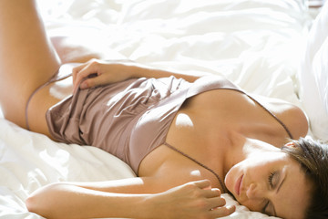 Young woman lying on bed, eyes closed