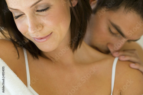 Young man kissing woman's shoulder, close-up