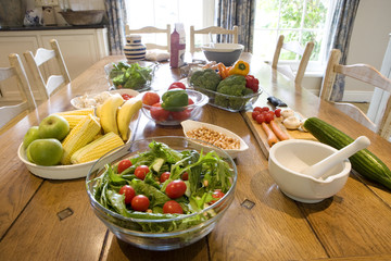 Salad, nuts, fruit, vegetables and pestle and mortar on dining table