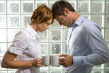 Businessman and woman holding mugs by glass block wall, heads and mugs touching, side view