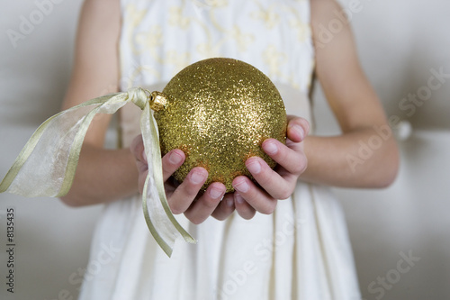 Young girl in a party dress, holding a Christmas decoration