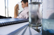 Glass of water by paperwork on desk, young businessman in background (differential focus)