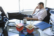 Young businessman asleep by takeaway cartons on desk, side view