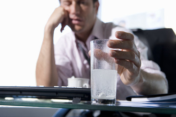 Young businessman with head in hand holding glass of water and soluble tablets, close-up of hand (differential focus)