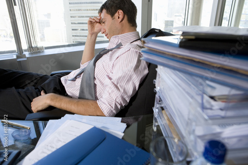 Young businessman slouching in chair by paperwork on desk, head in hand, side view