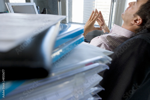 Young businessman leaning back in chair with hands together by files on desk (differential focus)