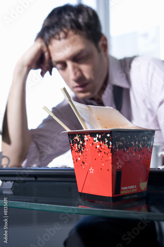 Young businessman by takeaway carton on desk, head in hand, eyes closed (differential focus)