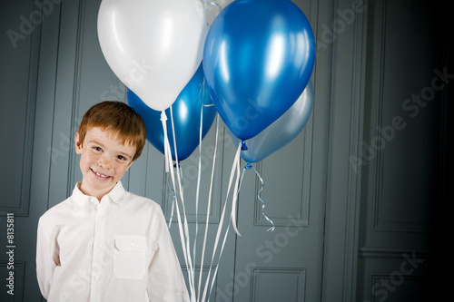 boy holding bunch of balloons
