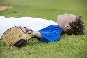 Boy laying down on the grass after a baseball game