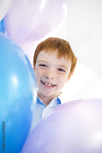 boy's face smiling framed by balloons