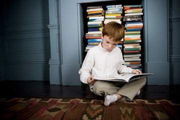 boy reading book sitting on the floor