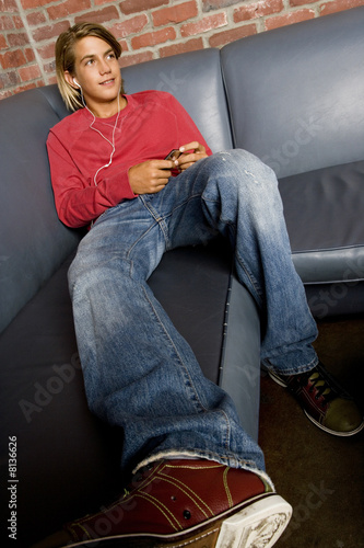 Teenage boy on a seat listening to music on mp3