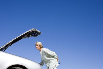 Senior woman experiencing car trouble, looking at engine, bonnet raised against clear blue sky, profile