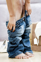Woman trying on jeans in the changing room of a shop