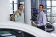 Car salesman standing with male customer in car showroom, holding brochure, smiling, side view, portrait