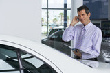 Car salesman standing beside new car in showroom, holding brochure, using mobile phone, smiling