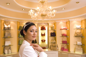 Young woman standing in front of designer handbags on shelf display in glamorous boutique, smiling, side view, portrait