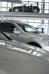 New silver saloon cars in car showroom, side view