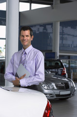 Car salesman standing beside new car in showroom, holding brochure, smiling, portrait
