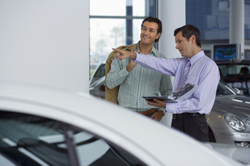 Car salesman pointing out new cars to male customer in showroom, holding brochure, smiling