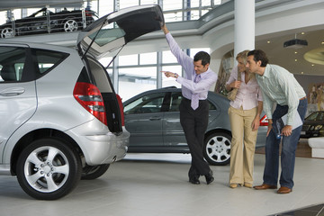 Car salesman showing couple new silver hatchback in car showroom, opening boot, smiling, side view