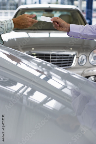 Car salesman passing business card to male customer in showroom, focus on hands, side view