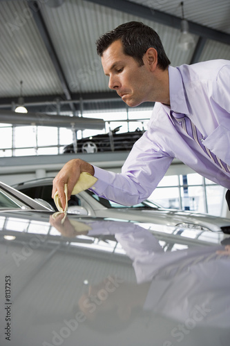 Car salesman polishing bonnet of new silver car with cloth in showroom (surface level)