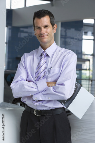Car salesman standing in showroom, holding brochure, arms folded, smiling, portrait