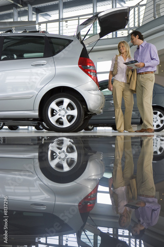 Couple looking at new silver hatchback in car showroom, man holding brochure, side view (surface level)