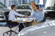 Car salesman and couple sitting at desk in large car showroom, two men shaking hands, smiling, side view