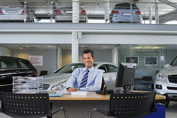 Car salesman sitting at desk in large car showroom, smiling, front view, portrait