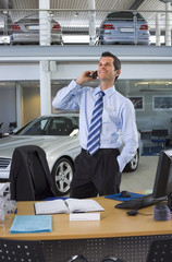 Car salesman standing beside desk in large car showroom, using mobile phone, smiling